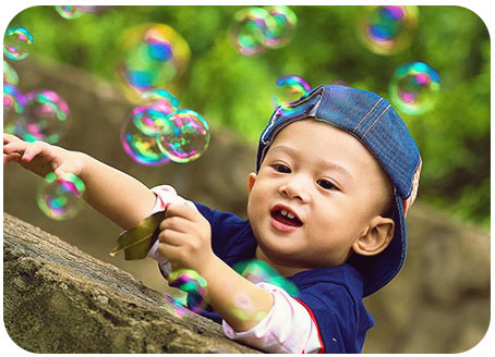 Outdoor Photograph of Children Playing with Bubbles